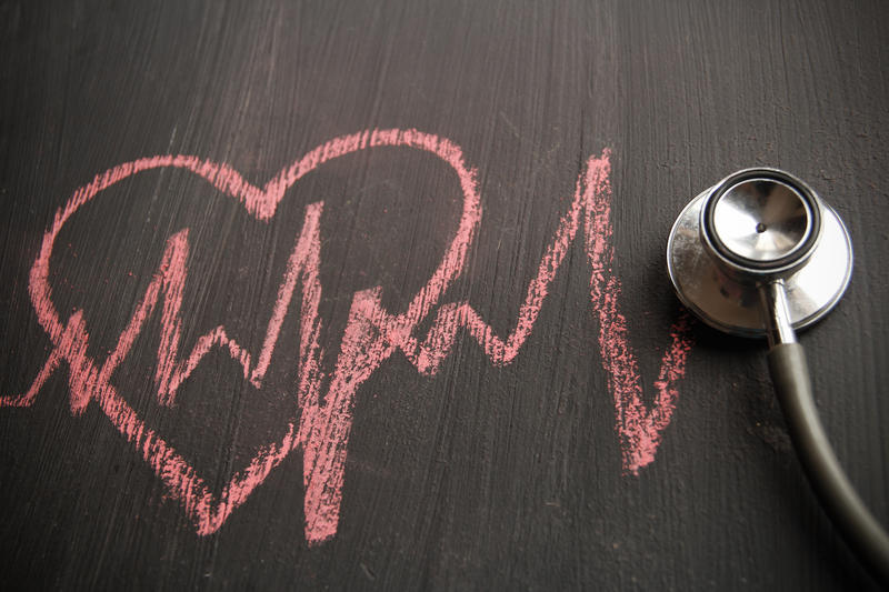 An illustration of heart drawn in chalk with heartbeat zigzag and a stethoscope.