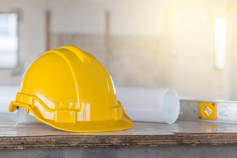 A yellow construction hat on a table next to a rolled piece of paper and a level.