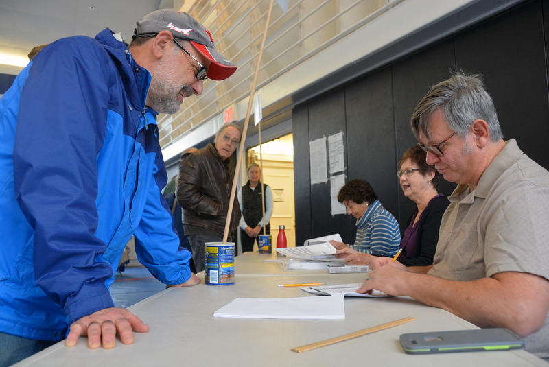 Dave Smith picks up his ballot from Ernie Ciccotelli at the Norwich polling place at Tracy Memorial Hall.