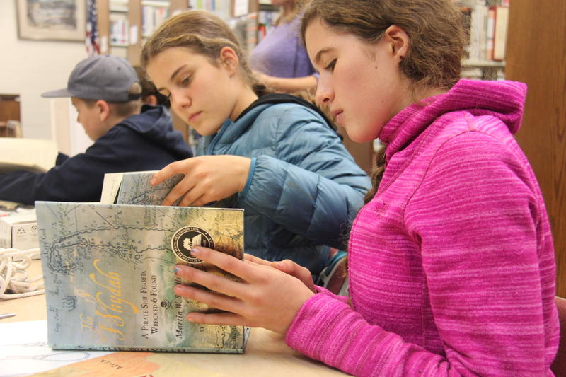 Two teenagers sit at a table looking at a book titled The Whydah: A Pirate Ship Feared, Wrecked and Found.