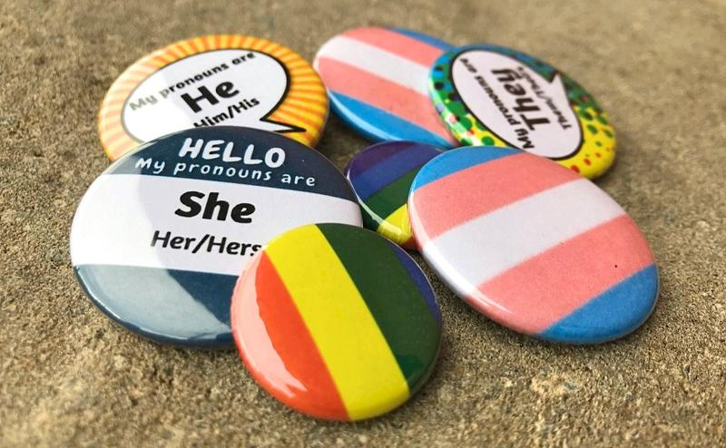 As transgender and non-binary communities across the country see increased visibility, they also face ongoing challenges and risks. Above, a transgender flag pin amid rainbow LGBTQ pins and others signaling a person's preferred pronouns.