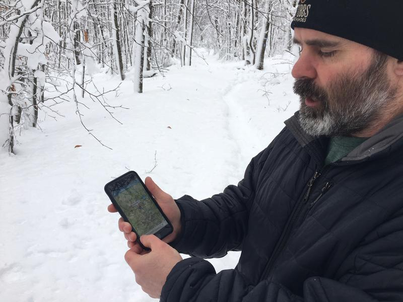 Matt Krebs, the operations and publications coordinator with the Green Mountain Club, uses a new digital map at Sherburne Pass. Snow is on the ground and trees in the background.