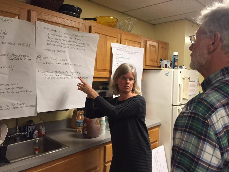 In this file photo, Dummerston School Board Chairwoman Kristina Naylor talks about the school's alternative governance plan in opposition to merging with a nearby district. Naylor stands in front of a poster hanging up and points to it.