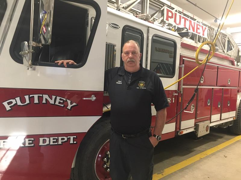 Putney Fire Chief Tom Goddard stands in front of a truck.