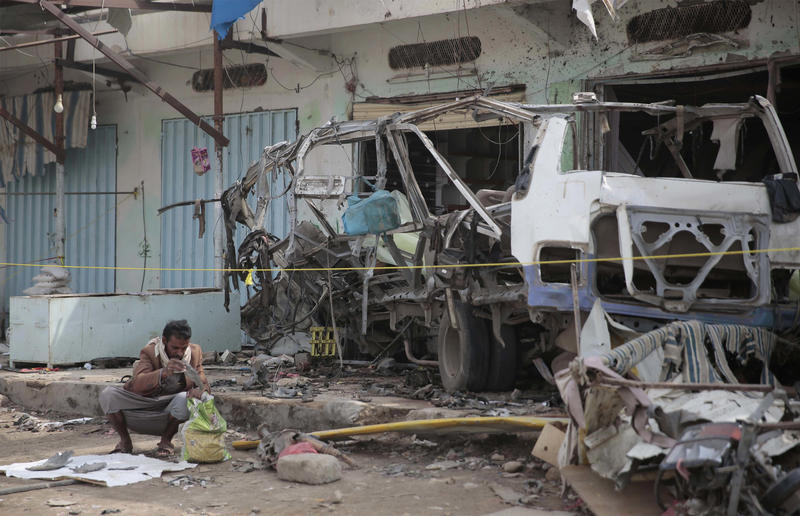 A man inspects the wreckage of a bus at the site of a deadly Saudi-led coalition airstrike in August in Saada, Yemen.