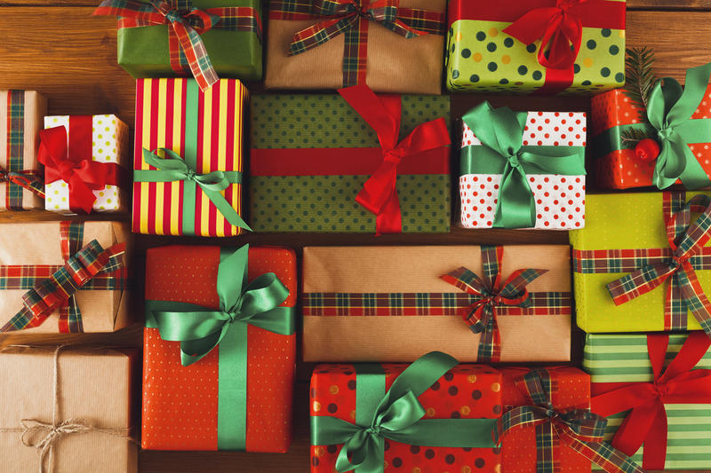 A collection of wrapped holiday gift boxes with bows.