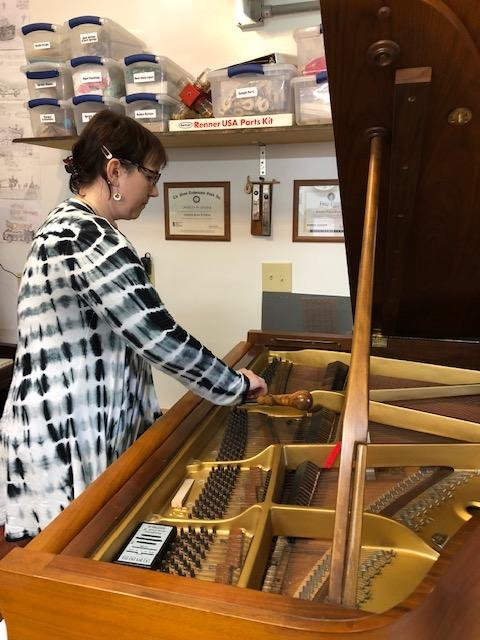 Rose Kinnick stands before an open piano