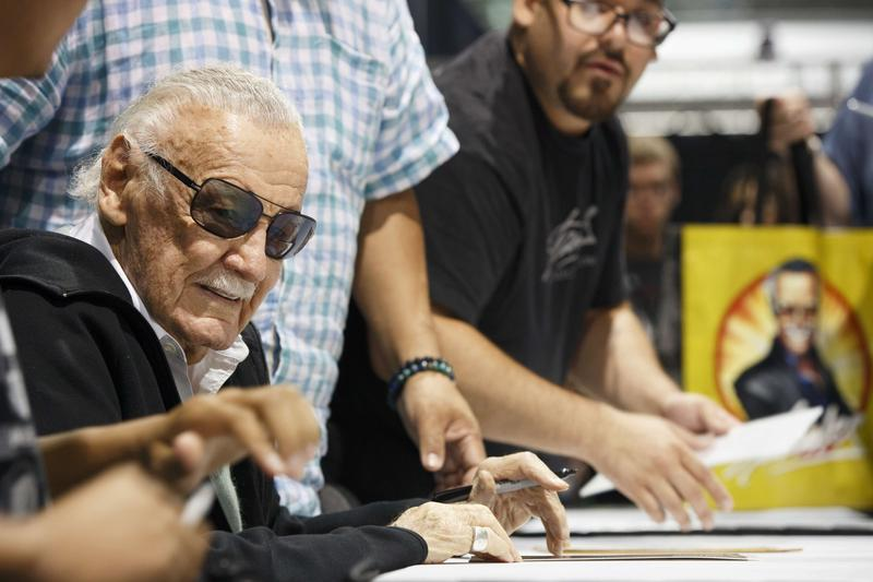 Stan Lee sits to sign autographs at Boston Comic Con in August 2017.