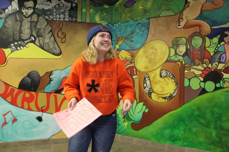 University of Vermont sophomore Syd Ovitt stands in front of a mural holding a sign that says Explain The Asterisk.