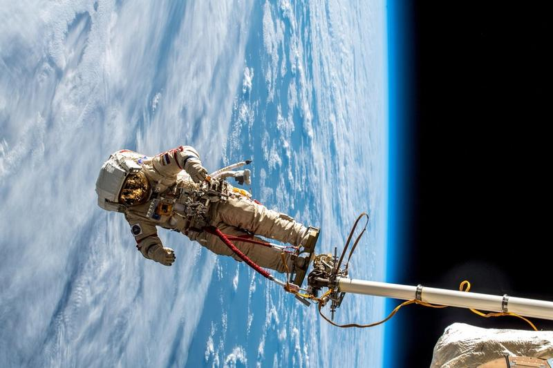 An astronaut on the International Space Station performs a spacewalk while tethered to the ISS on Dec. 13, 2018. A radiant blue earth is seen in the background.