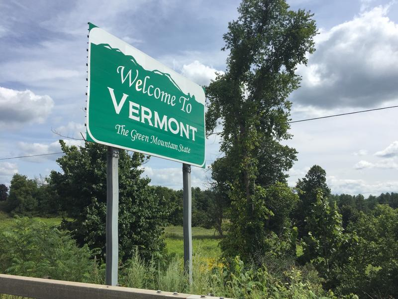 A sign on a summer day that says Welcome To Vermont The Green Mountain State with greenery in the background.