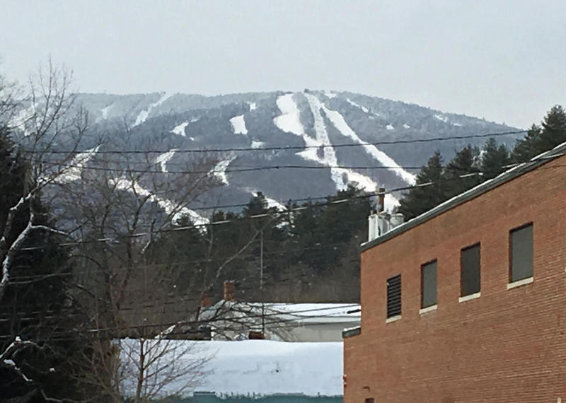 The tops of a couple buildings in Ludlow, with views of Okemo trails on a mountain in the distance against a gray-blue sky.