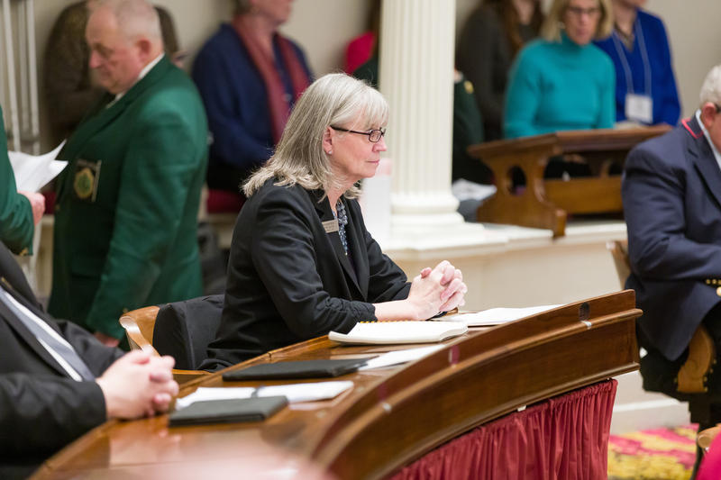 Rep. Pattie McCoy sits in the Vermont House chamber, looking ahead with hands folded.