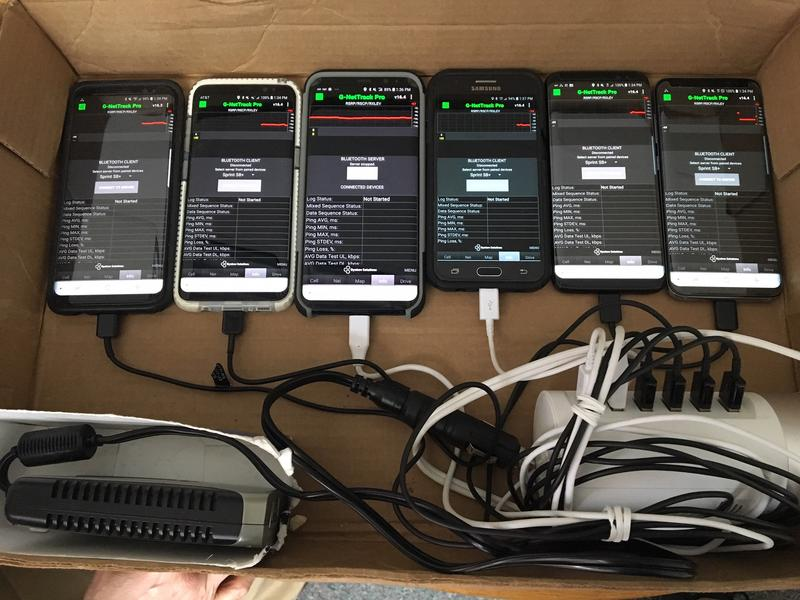 A row of six phones, each served by a different carrier with a variety of wires.