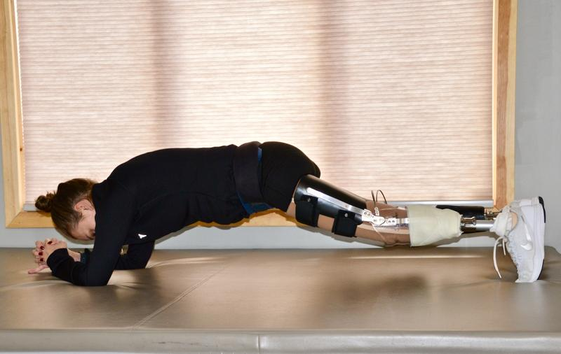 Stefanie Schaffer does a plank on a mat as part of her core excersies for physical therapy. She has two prosthetic legs.