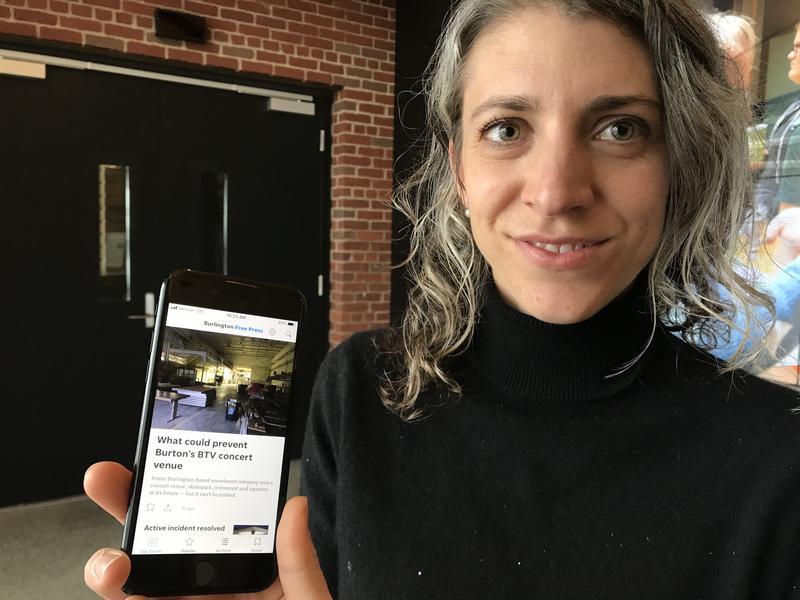 Burlington Free Press executive editor Emilie Stigliani holds up a phone displaying a Burlington Free Press news story.