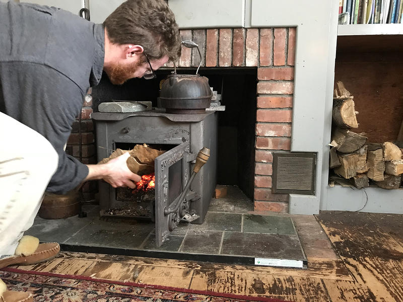 Emmet Moseley loads a log into his wood stove.