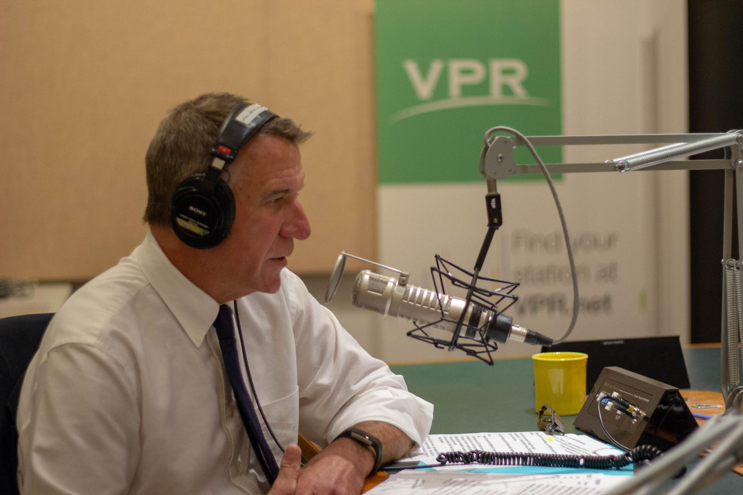 Gov. Phil Scott speaking into a microphone in the VPR Talk Studio