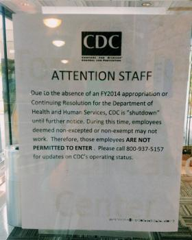 A sign posted on the entrance to the Atlanta-based Centers for Disease Control and Prevention tells employees and visitors the building is, with the exception of some staff, closed.