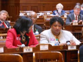 House Minority Leader Stacey Abrams (D-Atlanta), on the left, talks with Rep. Carolyn Hugley (D-Columbus) in the House chamber on the Legislature's 2014 opening day, January 13.