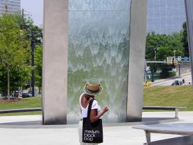A visitor to the National Center for Civil and Human Rights reads a quote from Margaret Mead on the center's fountain.