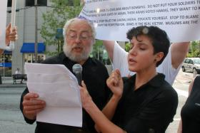 Steven Bell, left, and Regina Willis of Jewish Voices for Peace lead a prayer service for the victims of the recent Israeli-Palestinian conflict in front of the Israeli consulate Thursday in Midtown Atlanta. A silent protester with signs criticizing the Palestinian militant group Hamas stands behind.