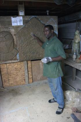 Sculptor Fred Ajanogha with one of his sculptures-in-progress planned for 352 University Avenue