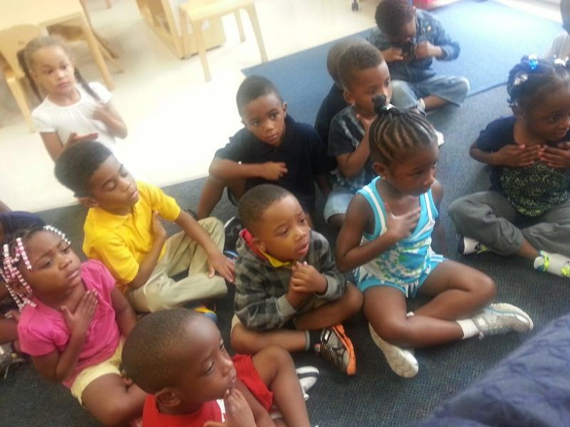 Children listen to their teacher read inside a Pre-kindergarten classroom.