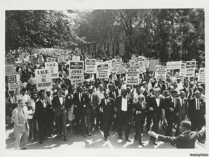 Dr. Martin Luther King, Jr., leading protestors with signs during the March on Washington.
