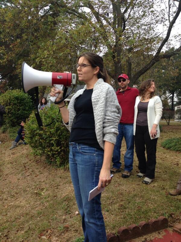 Marquardt addresses the protesters with a megaphone as they march toward the detention center.