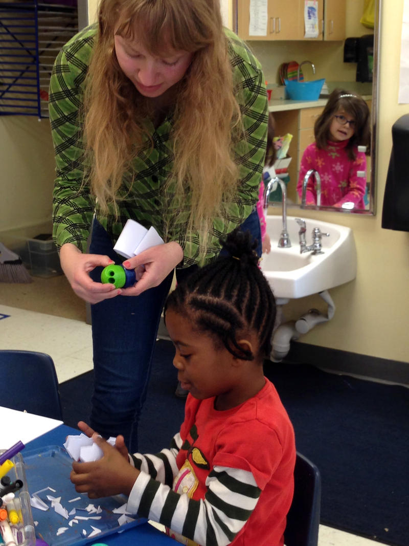 Halley Belacore, a paraprofessional at College Heights Early Childhood Learning Center, helps a student with an art project.
