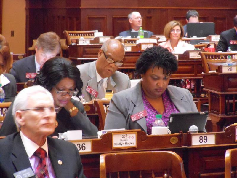 Scenes from the Capitol: House Minority Leader Stacey Abrams (D-Atlanta, right) and Rep. Carolyn Hugley (D-Columbus) look over legislation.  Behind them is Rep. Calvin Smyre (D-Columbus). In front is Phil Tucker, House Postmaster and Sergeant at Arms.