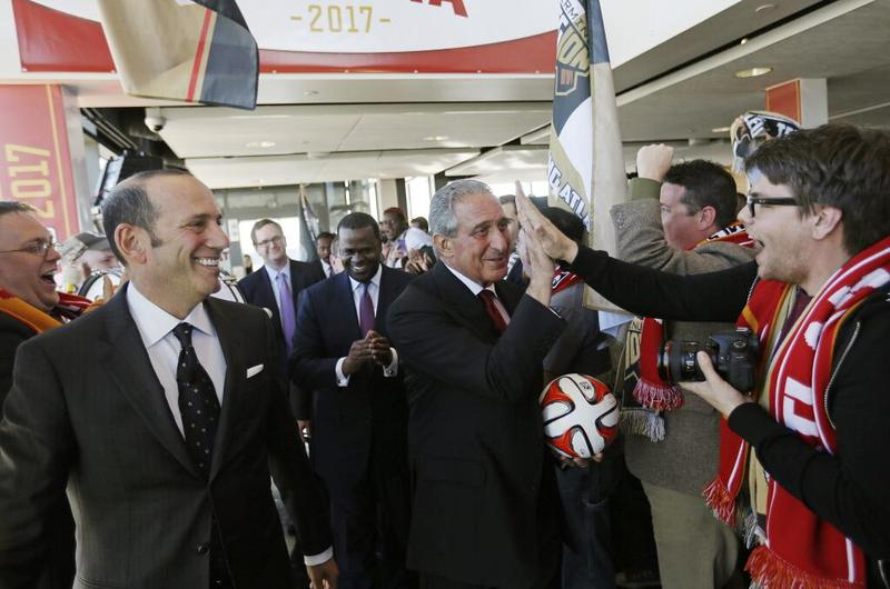 Arthur Blank (center) receives a high five from fans after announcing that a new MLS team will be coming to Atlanta.