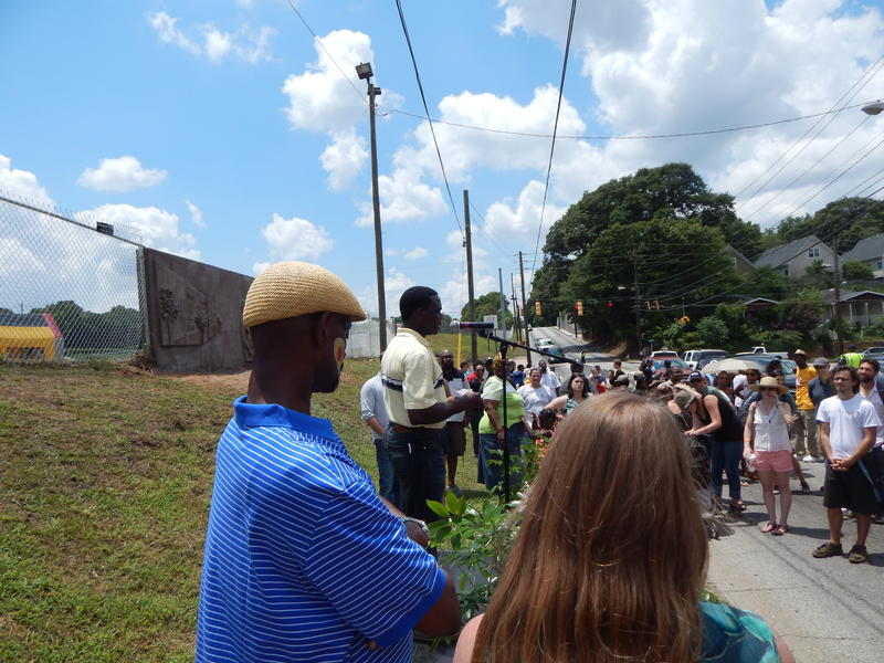 Artist Fred Ajanogha speaks to the crowd assembled at the July 12 unveiling of the artwork at 352 University Avenue.