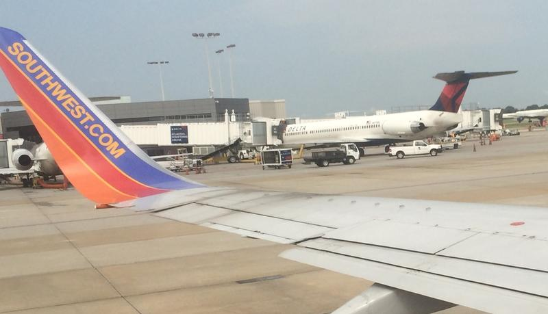 A Southwest Airlines B-737 taxis past a Delta jet parked at Atlanta's Hartsfield-Jackson International Airport.