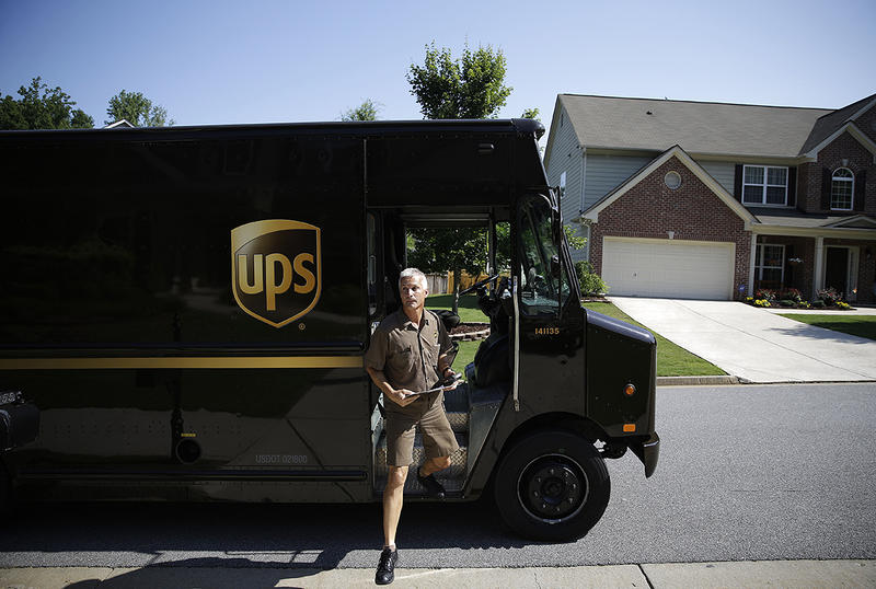 United Parcel Service driver Marty Thompson steps off a truck while making a delivery in Cumming, Ga.