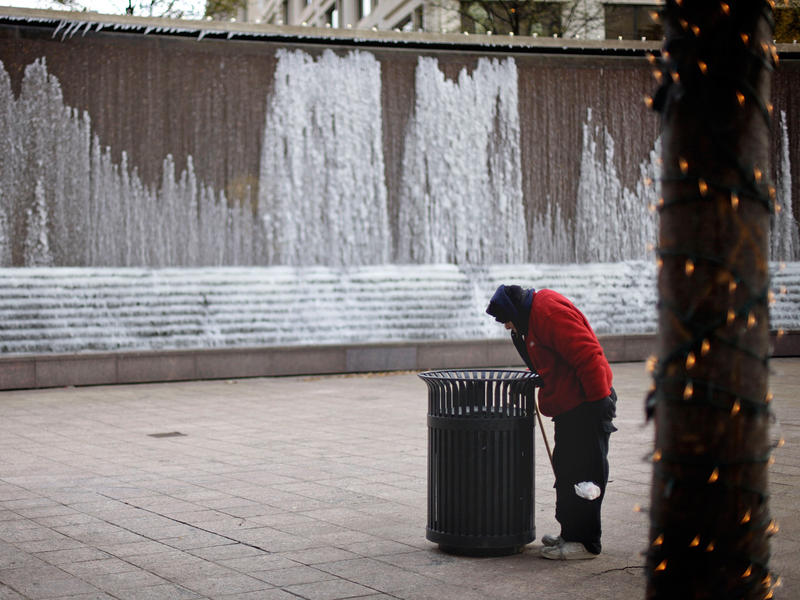 Peggy Ann Schnitzius, 77, looks inside a garbage bin while braving the cold weather in front of a frozen fountain Monday, Dec. 13, 2010, in downtown Atlanta.