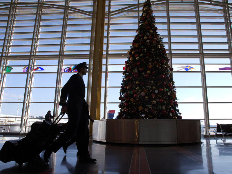 A pilot walks past a Christmas Tree at Reagan National Airport on Christmas Eve, Tuesday, Dec. 24, 2013.