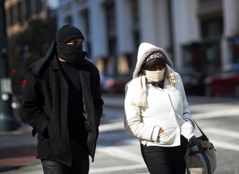 Pedestrians are bundled up while walking through downtown, Tuesday, Nov. 18, 2014, in Atlanta. Temperatures plunged into the 20s in many parts of Georgia and dropped to 13 in one spot in the mountains as cold air settled over the state.