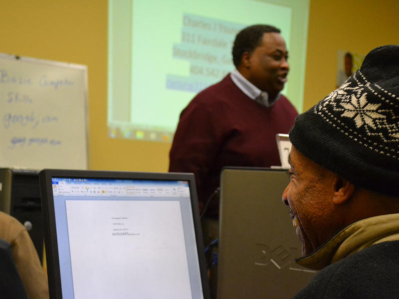 Christopher Martin attending a computer class at the Atlanta-Fulton Public Library, taught by librarian Charles Young.