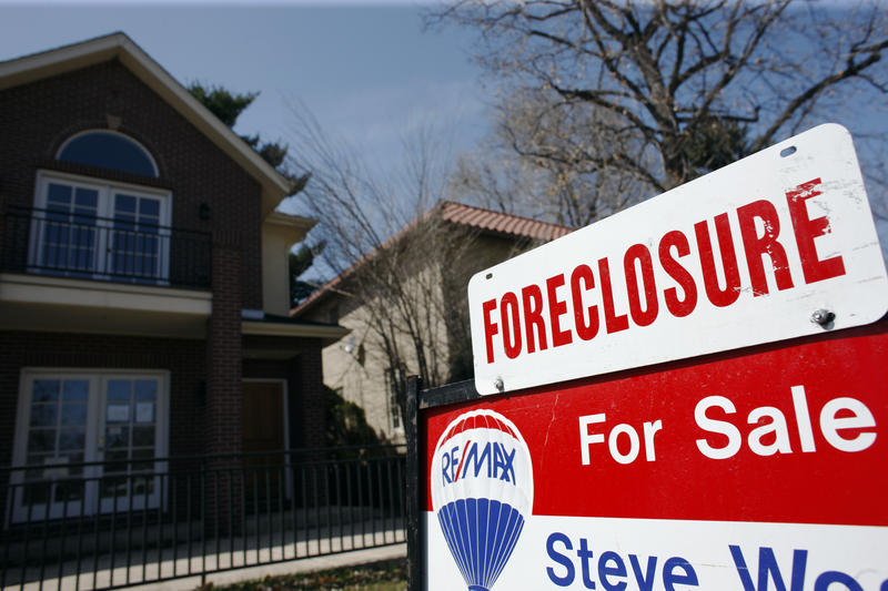 In this April 4, 2010 file photo, a foreclosure sign sits atop a for sale sign in front of a single-family home tops the for sale sign in Denver on Sunday, April 4, 2010.
