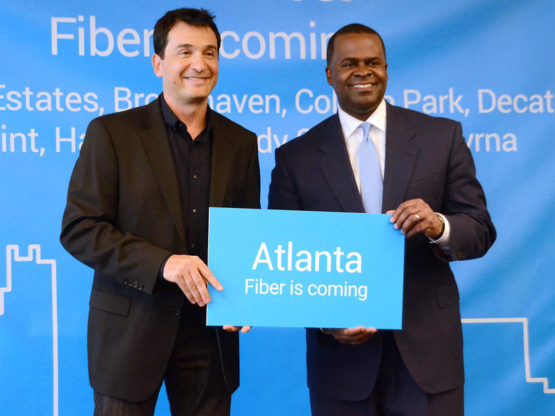 Atlanta Mayor Kasim Reed, right, and Google Fiber Marketing Director Scott Levitan hold a sign announcing that Google Fiber is coming to Atlanta. Some HUD housing facilities will offer residents who qualify free Google Fiber service.