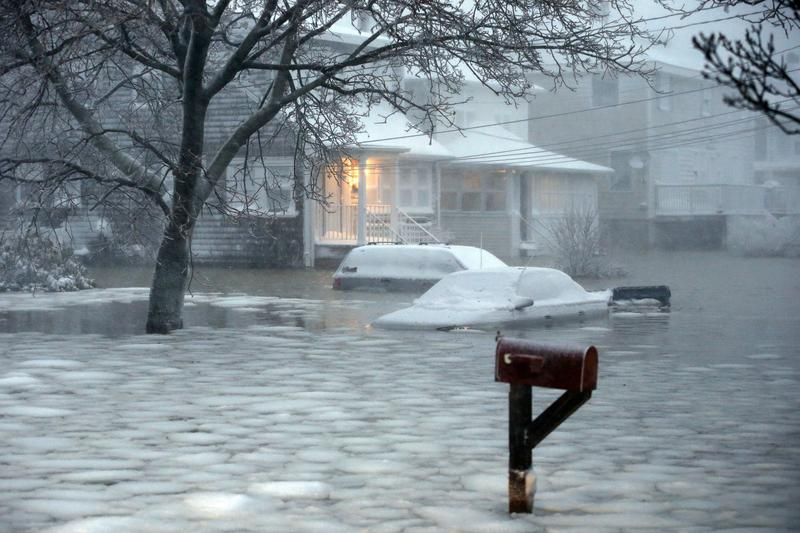 Water floods a street on the coast in Scituate, Mass., Tuesday, Jan. 27, 2015. A storm packing blizzard conditions spun up the East Coast early Tuesday, pounding parts of coastal New Jersey northward through Maine with high winds and heavy snow.