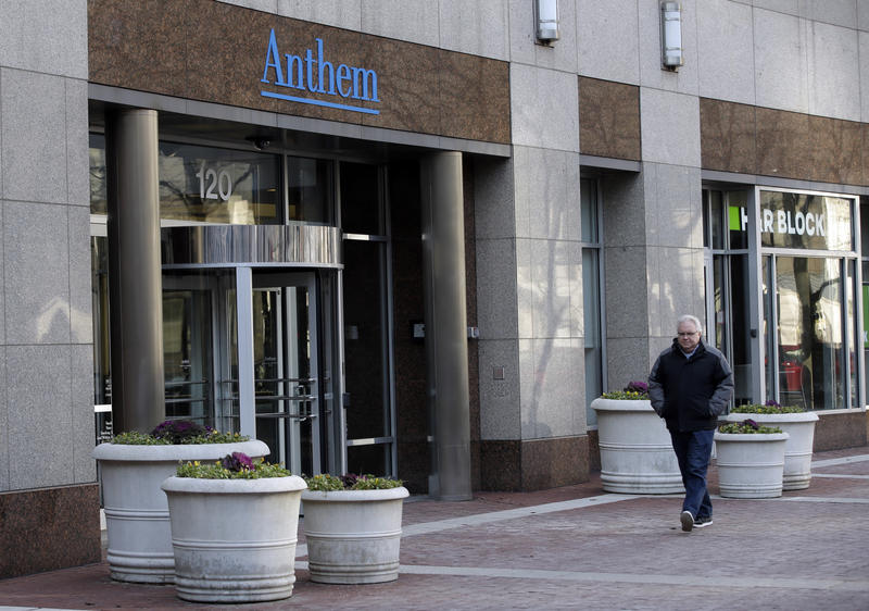 A pedestrian walks past the corporate headquarters of health insurer Anthem, formerly known as Wellpoint, on Wednesday, Dec. 3, 2014 in Indianapolis. The Blue Cross Blue Shield insurer sells insurance in several states under the Anthem brand, which was th