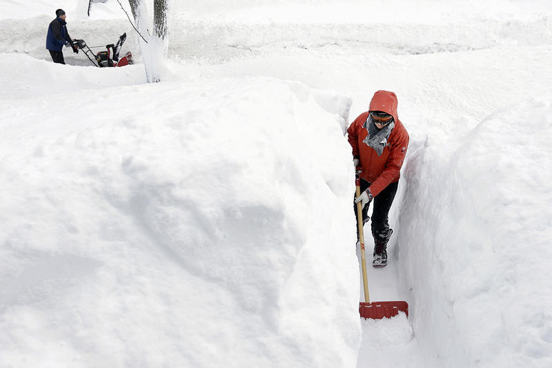Kim Taylor, of Norwood, Mass., right, shovels a path in the snow in front of her home Sunday, Feb. 15, 2015, in Norwood. A storm brought a new round of wind-whipped snow to New England on Sunday.
