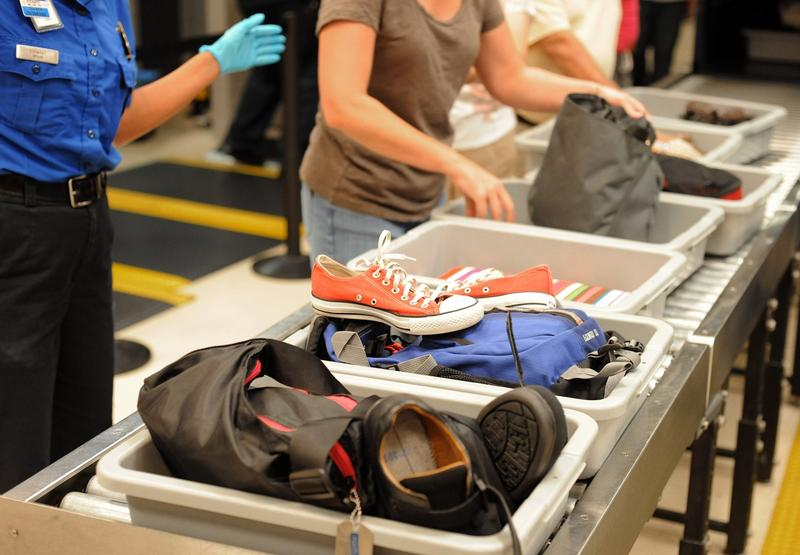 In this Aug. 3, 2011, file photo, airline passengers retrieve their scanned belongings while going through the Transportation Security Administration security checkpoint at Hartsfield-Jackson Atlanta International Airport, in Atlanta.