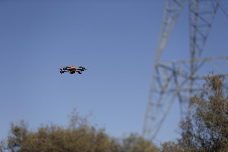 In this Oct. 16, 2014 picture, an unmanned aircraft flies near a tower carrying long-distance electric transmission lines near Boulevard, Calif.
