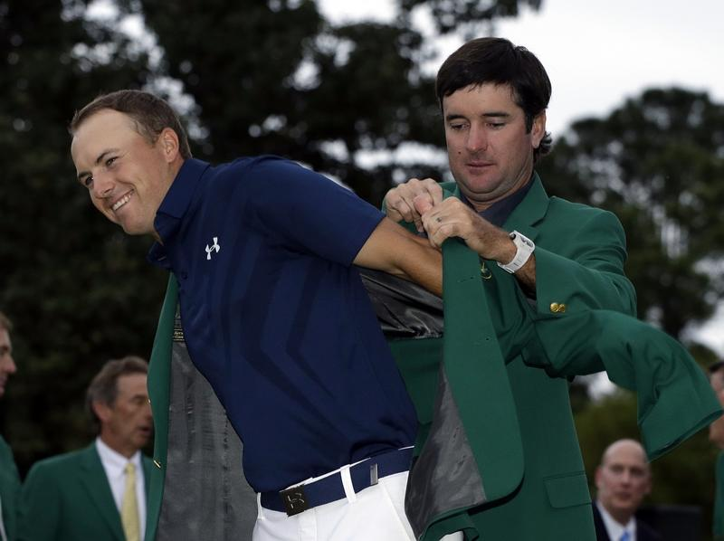 Bubba Watson helps Jordan Spieth put on his green jacket for the second time after winning the Masters golf tournament Sunday, April 12, 2015, in Augusta, Ga.