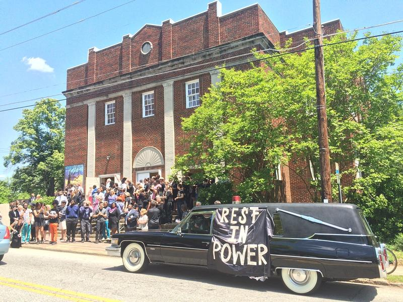 An empty hearse and protesters outside Oakhurst Baptist Church.