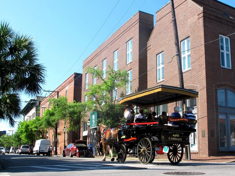 This April 23, 2015 photo shows a horse-drawn carriage moving through the historic district in Charleston, S.C.